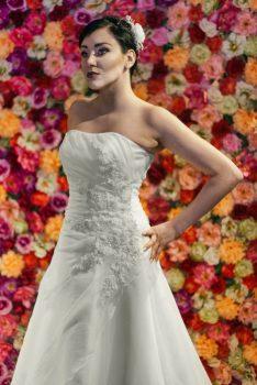 Brautkleid Model 311. Das A-förmige Hochzeitskleid mit einem offenen Ausschnitt. Eine asymmetrische Drapierung aus Organza ist seitlich mit handbestickten Applikationen verziert.