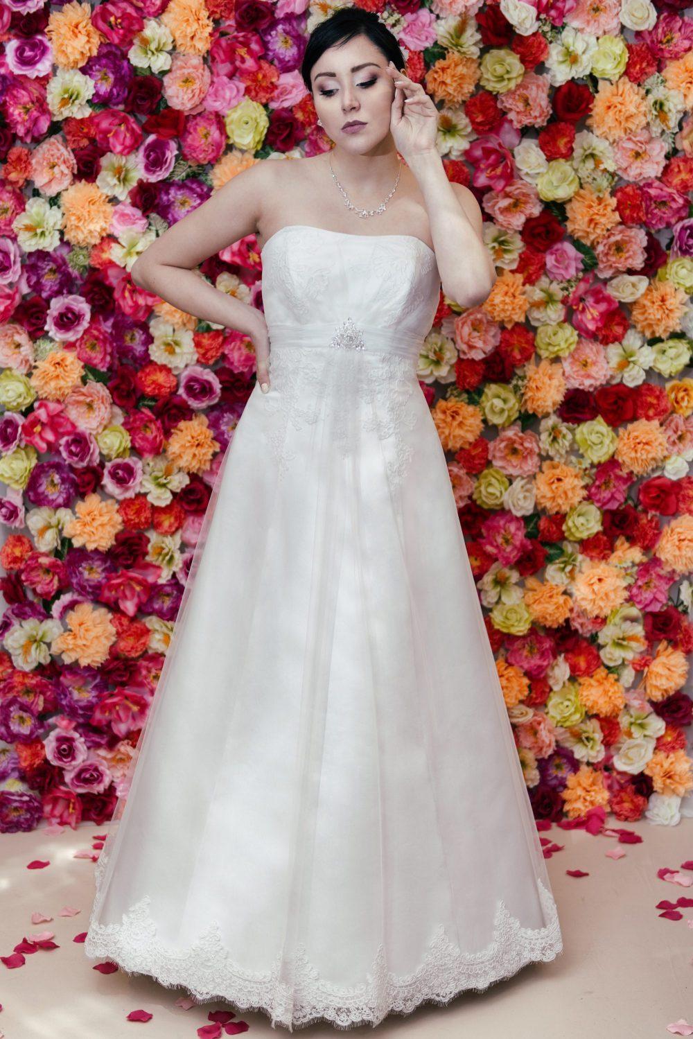 Suknia ślubna litera A zdobiona koronką i kryształową broszką.