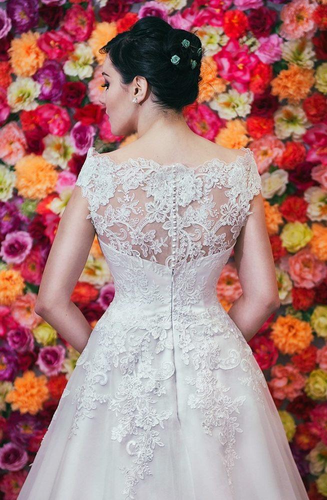 Suknia ślubna litera A z koronkowym dekoltem w kształcie łódki zapinanym na guziki.