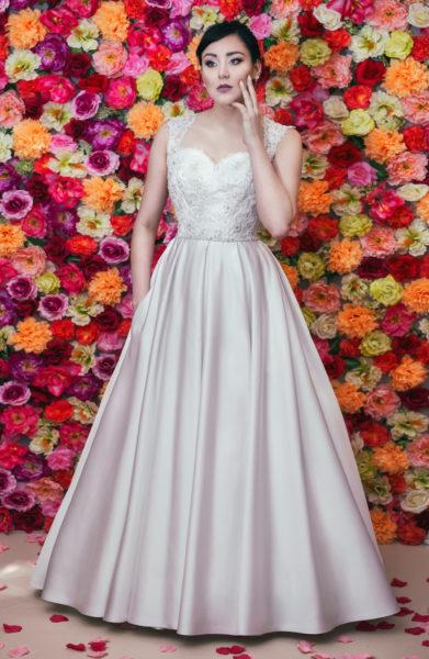 Suknia ślubna zdobiona wyszywaną koronką i satynową spódnicą z kieszeniami.