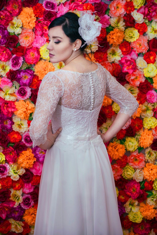 Suknia ślubna Model 711 z zakrytym dekoltem zapinanym na guziczki.